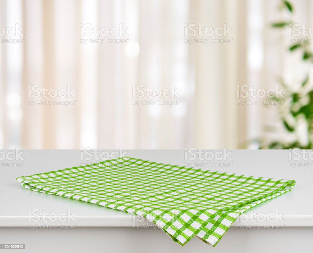 Green checkered kitchen towel on table over defocused curtain background stock photo