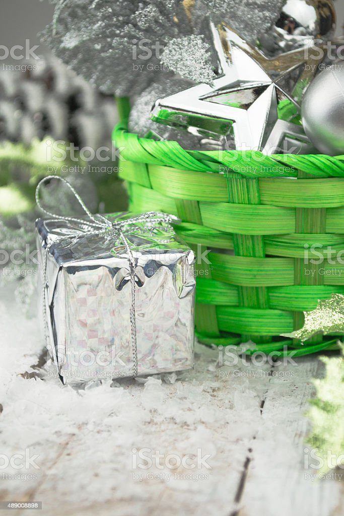 Green Christmas basket with silver toys on a white wood stock photo