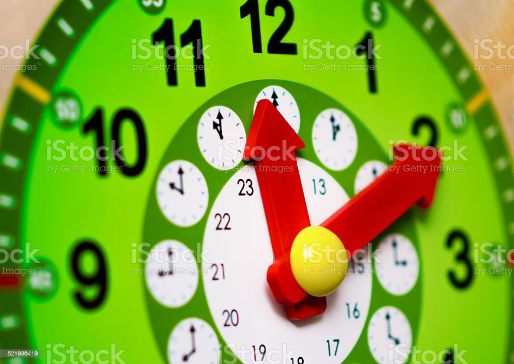 Green clock with red arrows stock photo