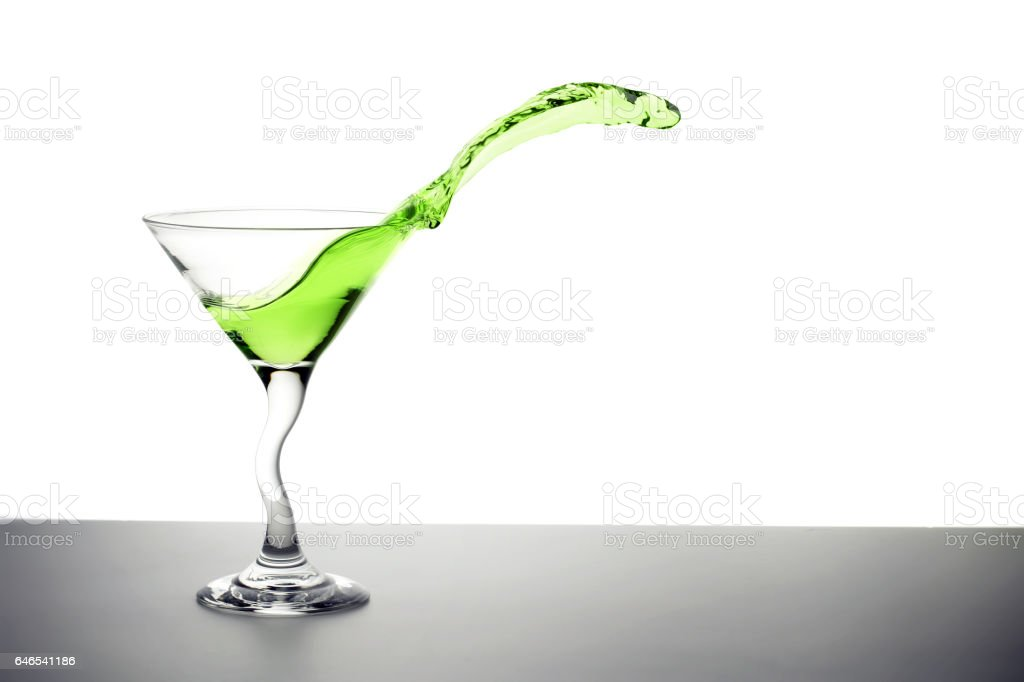 green cocktail splashing out of a martini glass stock photo
