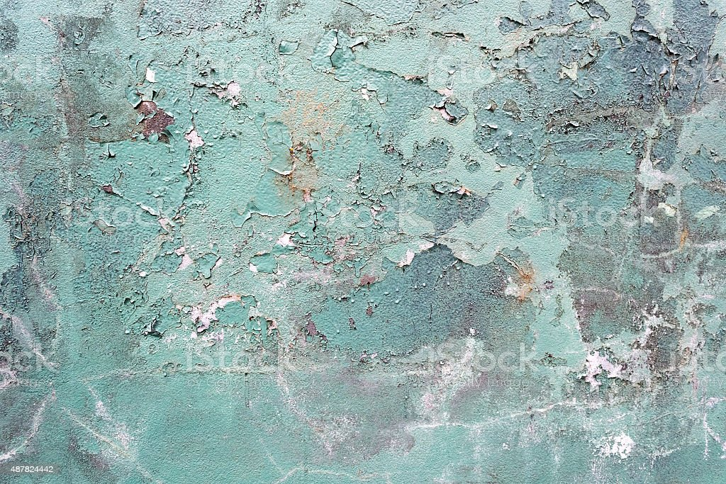 Green concrete cracked painted wall, damaged surface stock photo