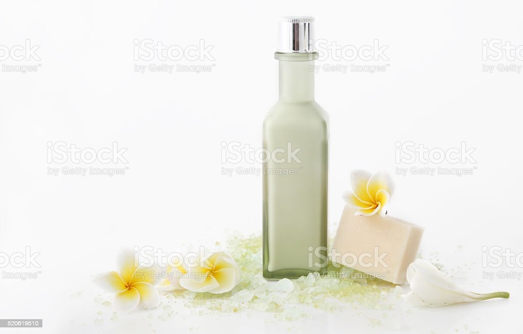 Green cosmetic bottle with bath salt and frangipani flowers stock photo