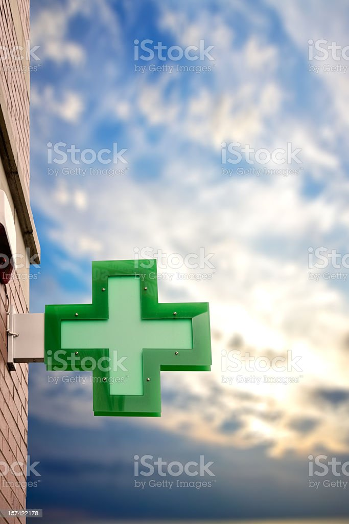 A green cross light box on the side of a building stock photo