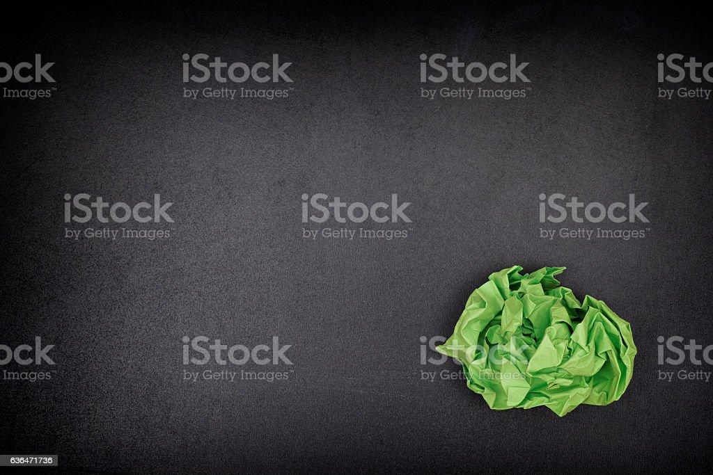 Green crumpled paper ball on a blackboard stock photo