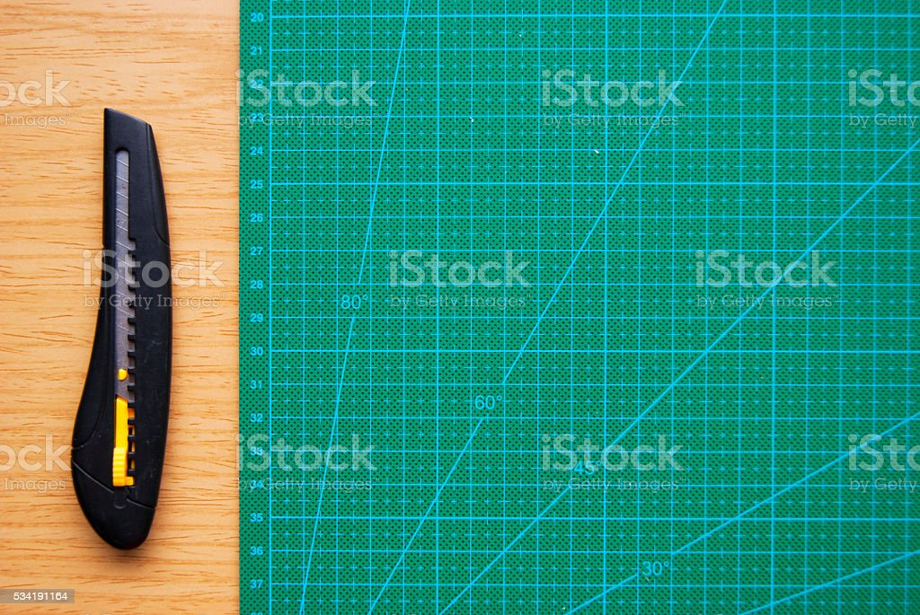 Green Cutting Mat and Letter Opener on Wood Desk stock photo