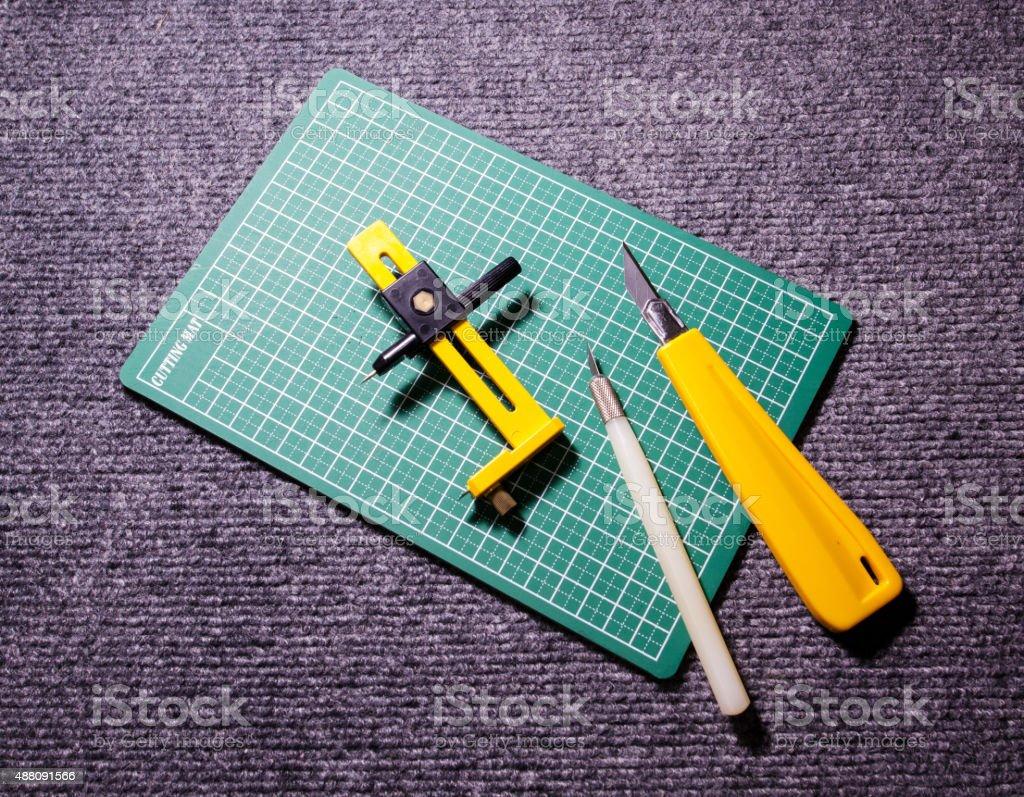 Green cutting mats with cuter on carpat stock photo