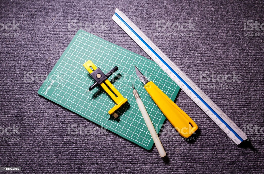 Green cutting mats with scale ruler and cuter on carpat stock photo