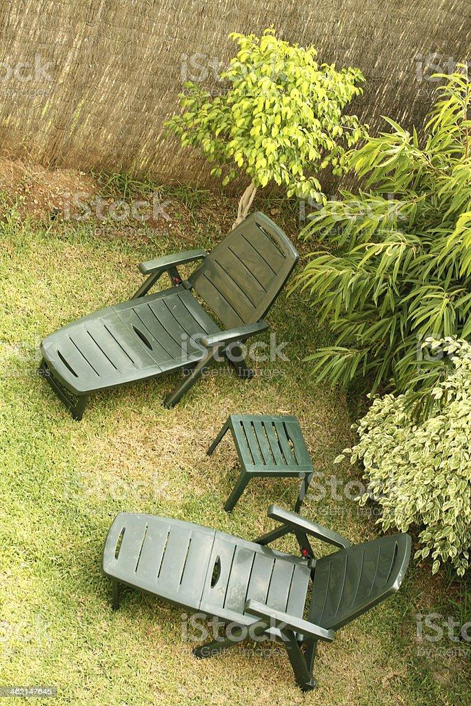 Green Deckchairs in Garden stock photo