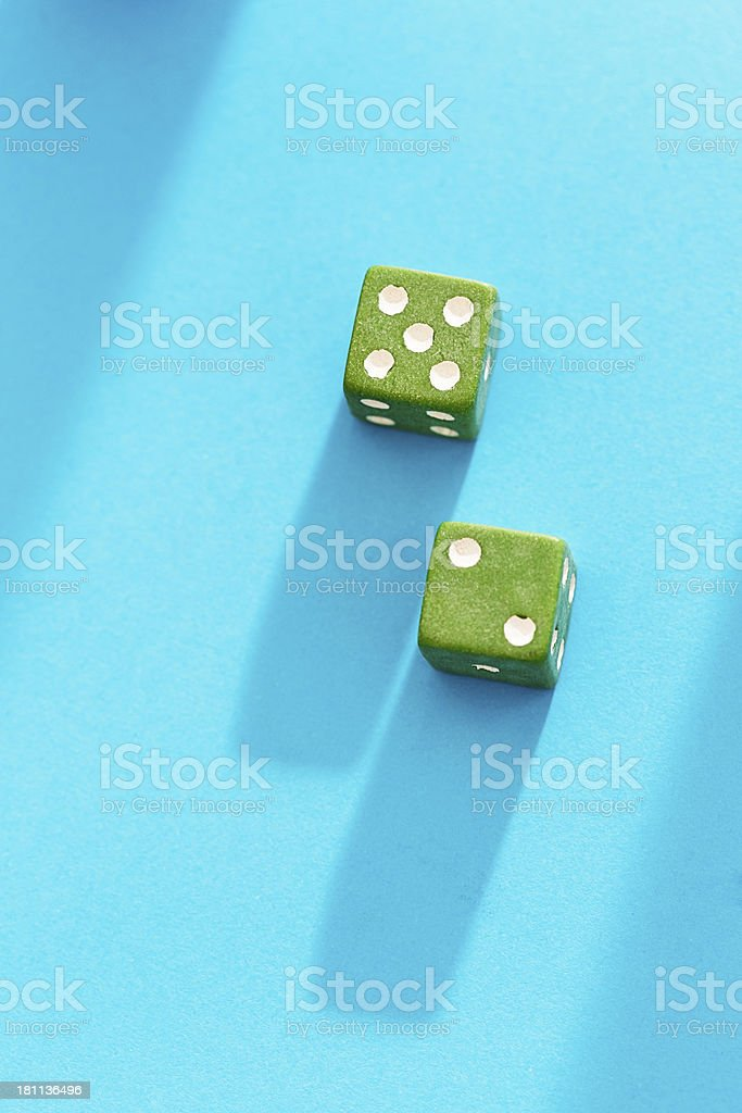 Green dice score 7 against blue background stock photo