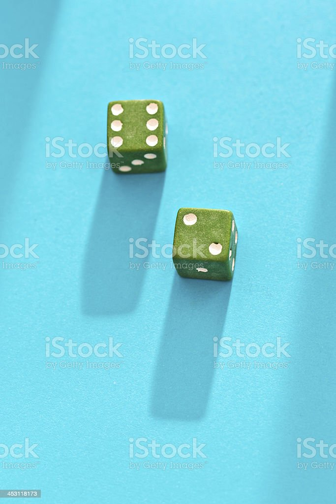 Green dice show score of 8 on blue background royalty-free stock photo