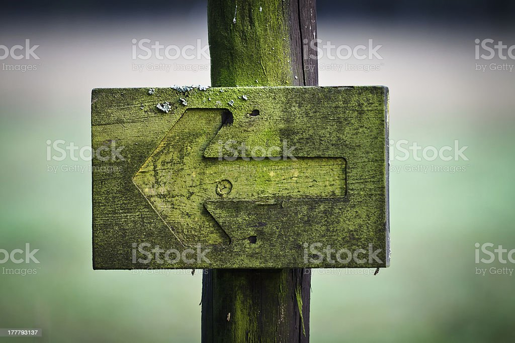 Green directional sign in the foothpath stock photo