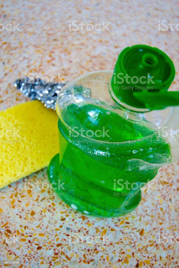 Green Dish Soap, Yellow Sponge, Metal Scrubber, Wet Kitchen Counter stock photo