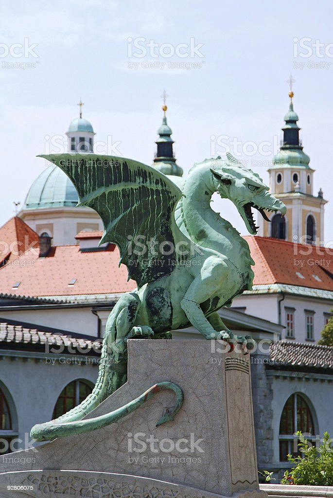 A green dragon statue perched atop a concrete platform stock photo