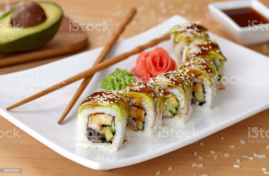 Green dragon sushi roll with eel, avocado, cucumber, wasabi and stock photo