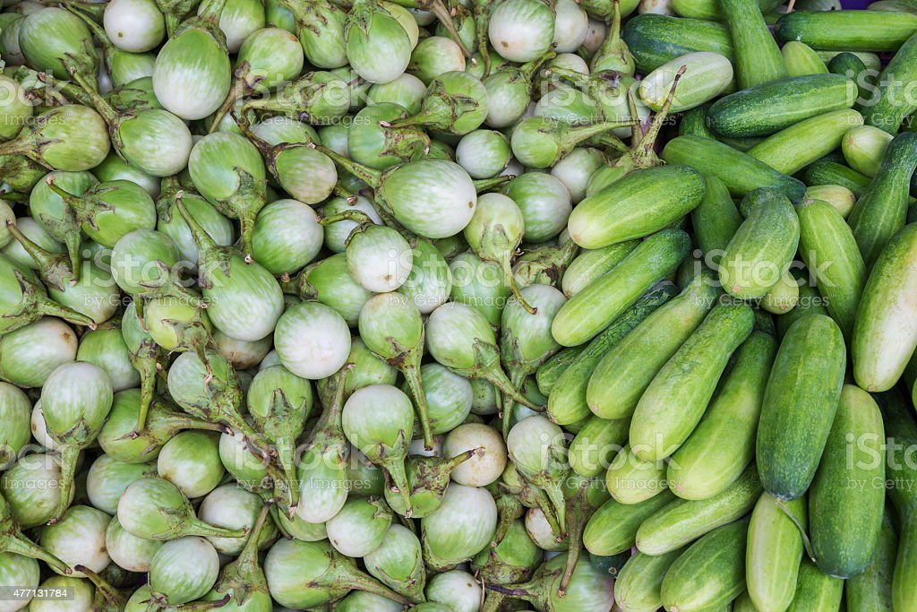 Green eggplants and cucumbers for sale at market, Thailand royalty-free stock photo