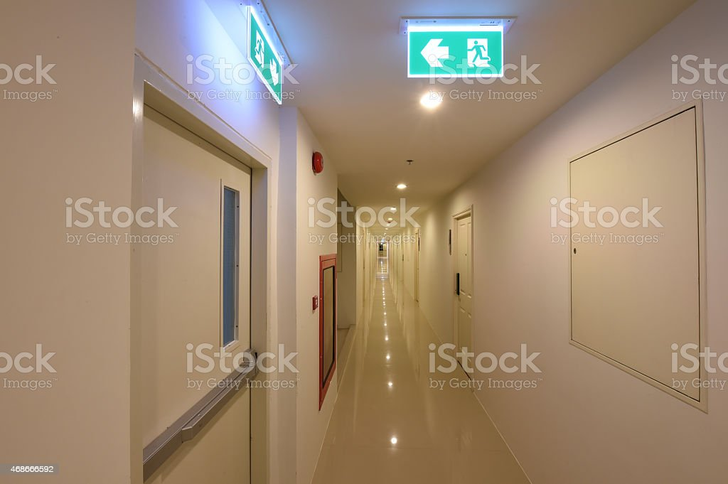 green emergency exit sign showing the way to escape stock photo