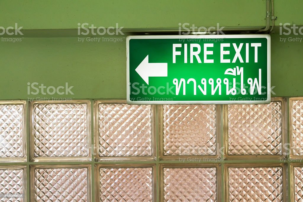 Green emergency fire exit sign showing the way to escape. stock photo