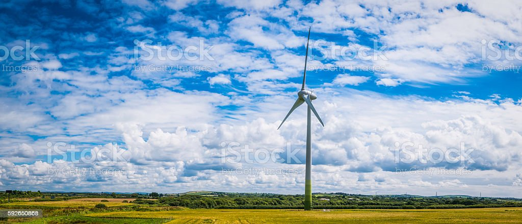 Green energy environmentally friendly wind turbine generating electricity in field stock photo