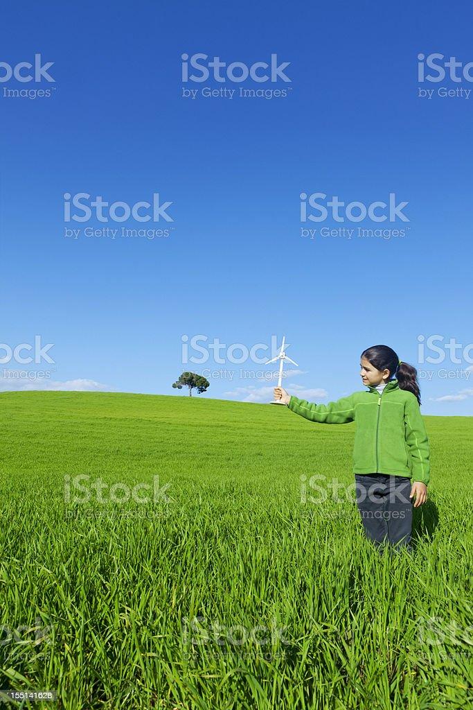 Green energy: girl holding wind turbine royalty-free stock photo