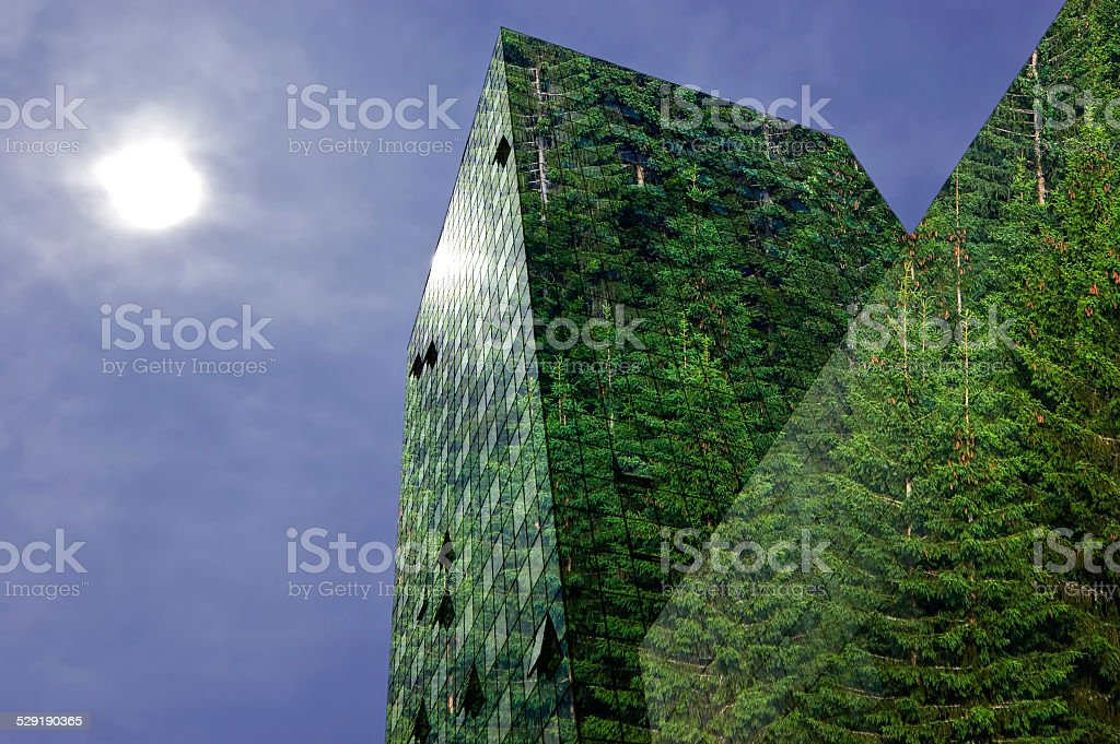 Green energy : modern city building covered with spruce forest stock photo