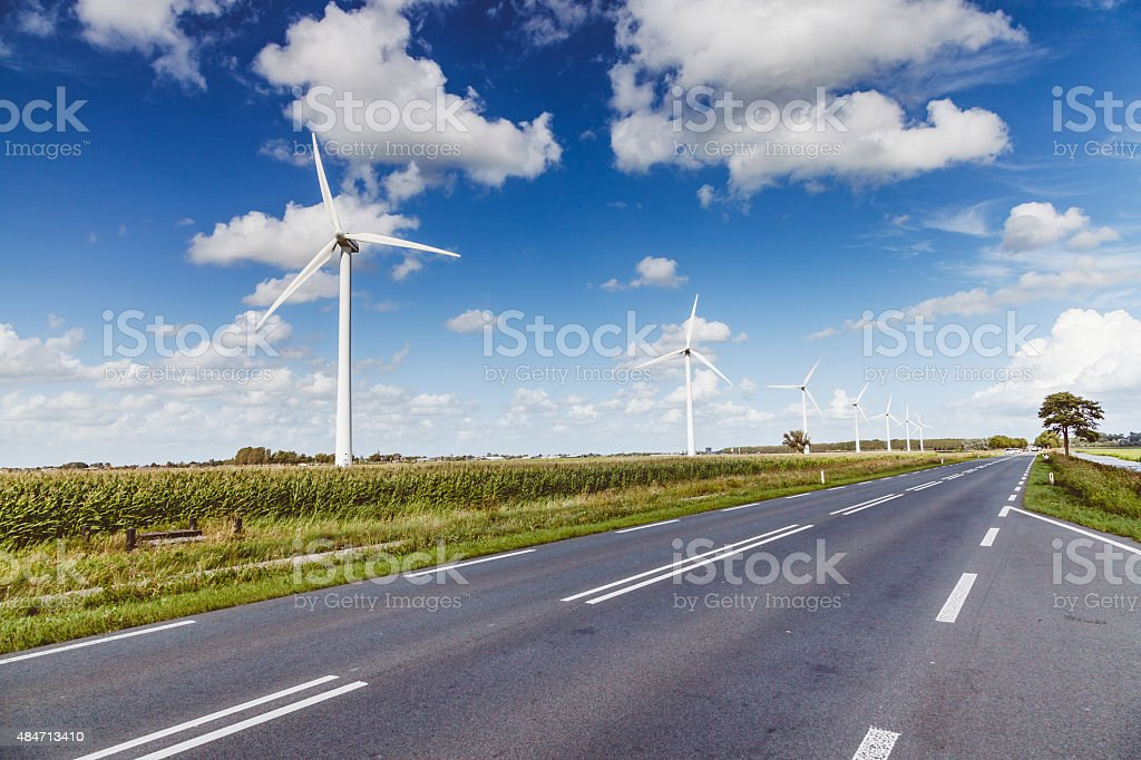 Green energy - Wind turbines and a dutch road stock photo