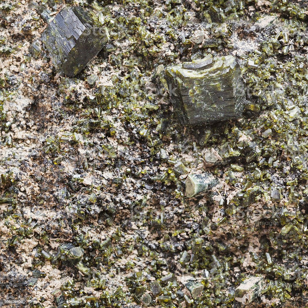 green epidote crystals on rock close up stock photo