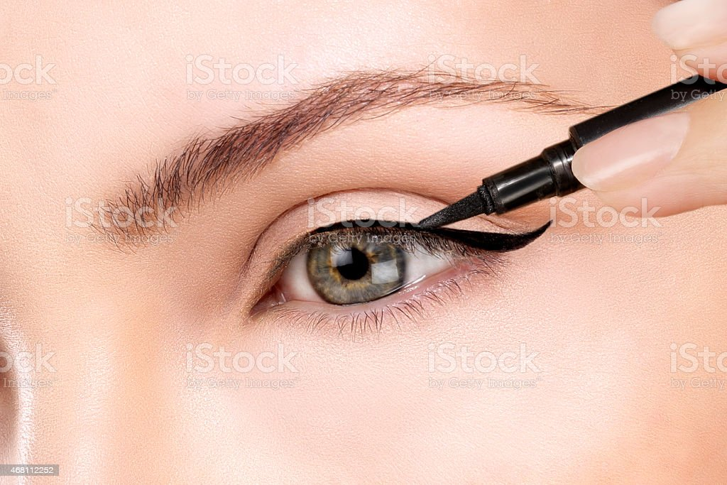 Green eyed beautiful model applying foundation with a brush stock photo