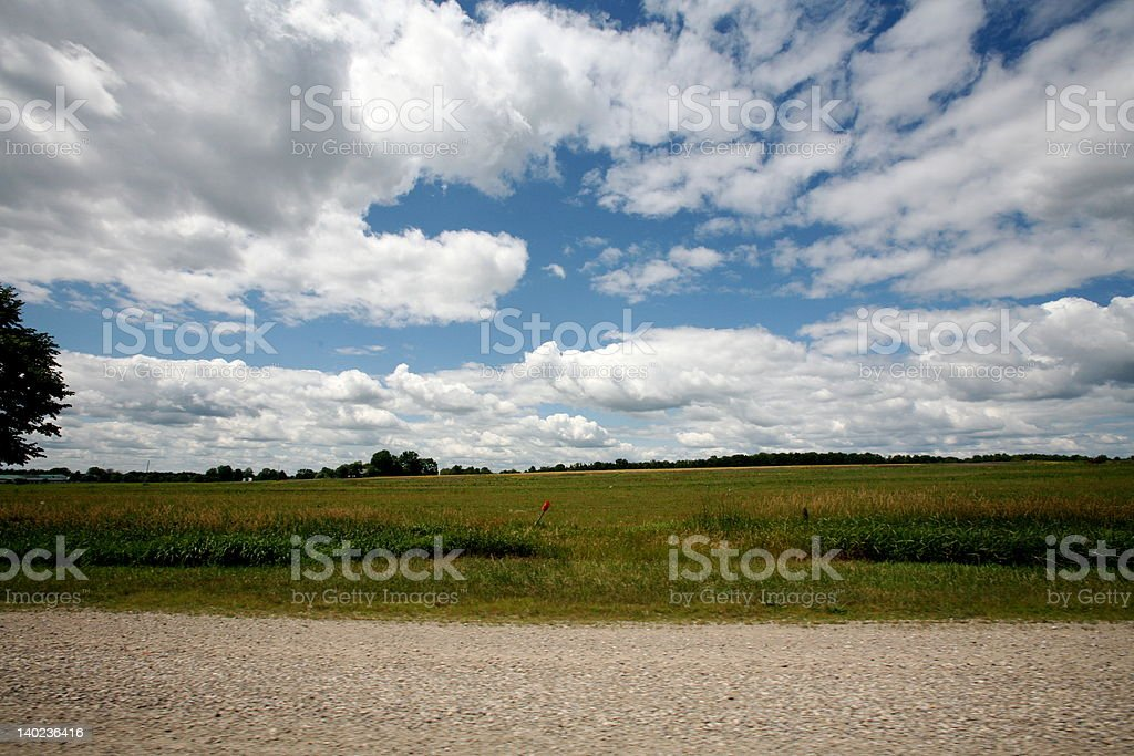 green farmland with intense clouds royalty-free stock photo