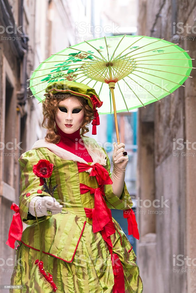 Green Female Mask with Parasol, Venice Carnival, Arsenale, Italy, Europe stock photo