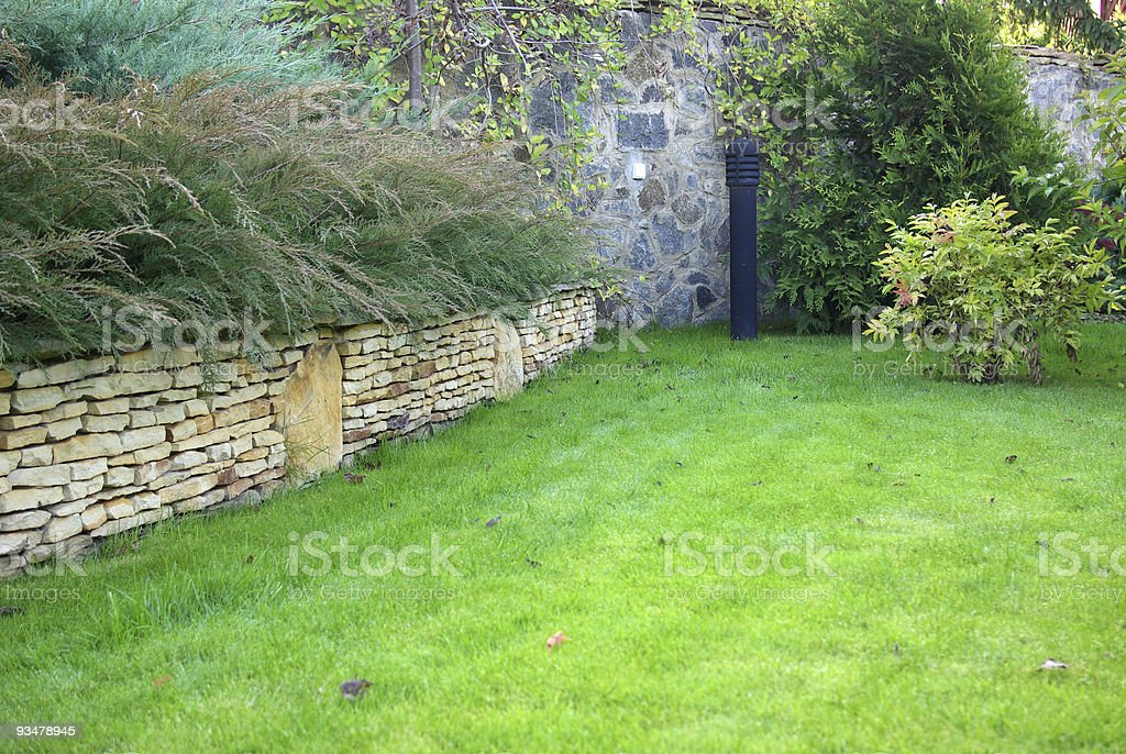 A green fern garden with layered stone walls royalty-free stock photo