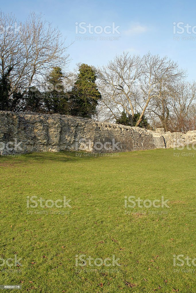Green field, blue sky, stone wall stock photo