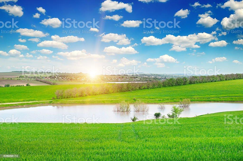 green field, lake and sunrise stock photo