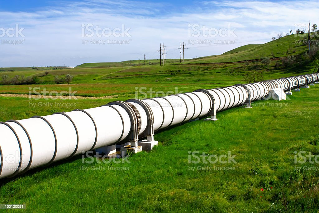 A green field on a Spring day with an industrial gas pipe stock photo