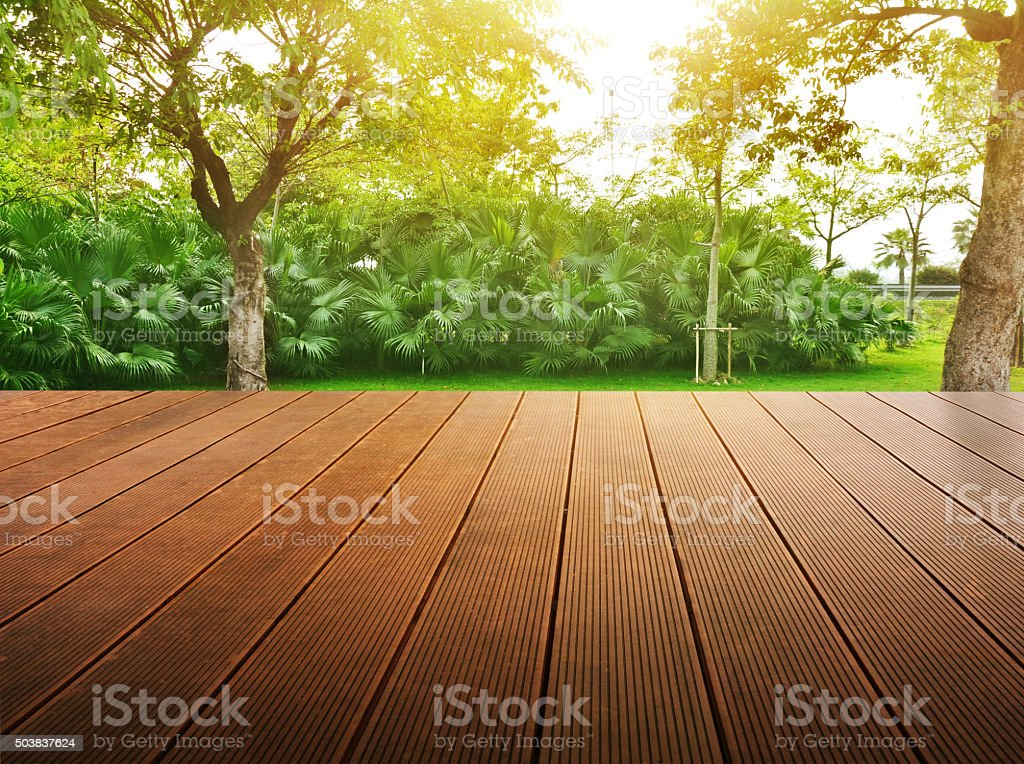 Green field under the sun. Wood planks floor  background. stock photo