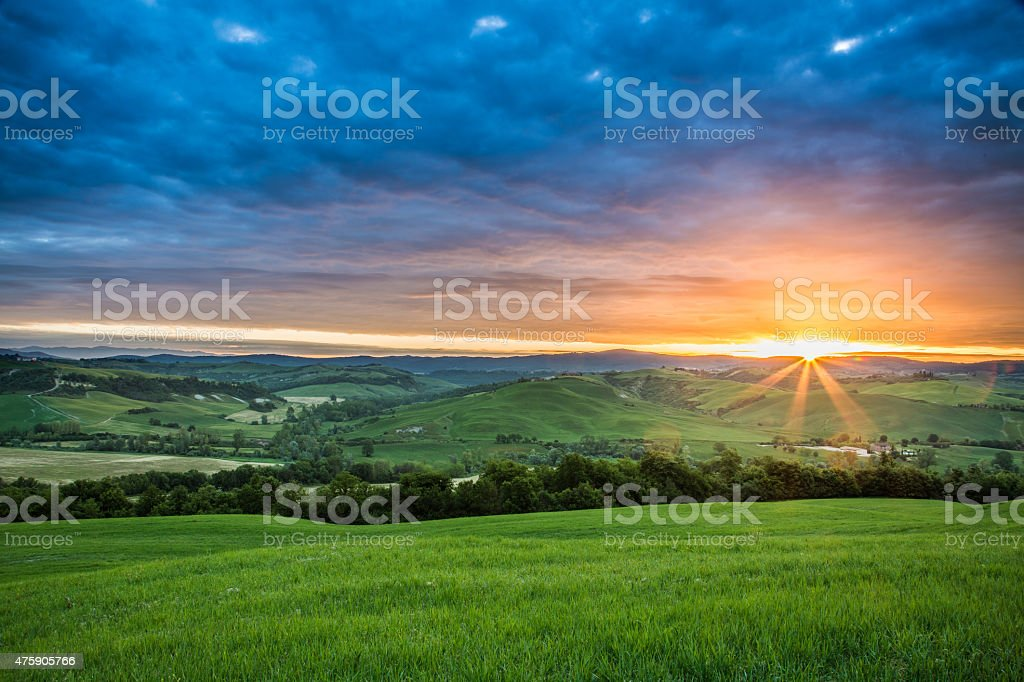 Green fields in the valley at sunset, Tuscany, Italy stock photo