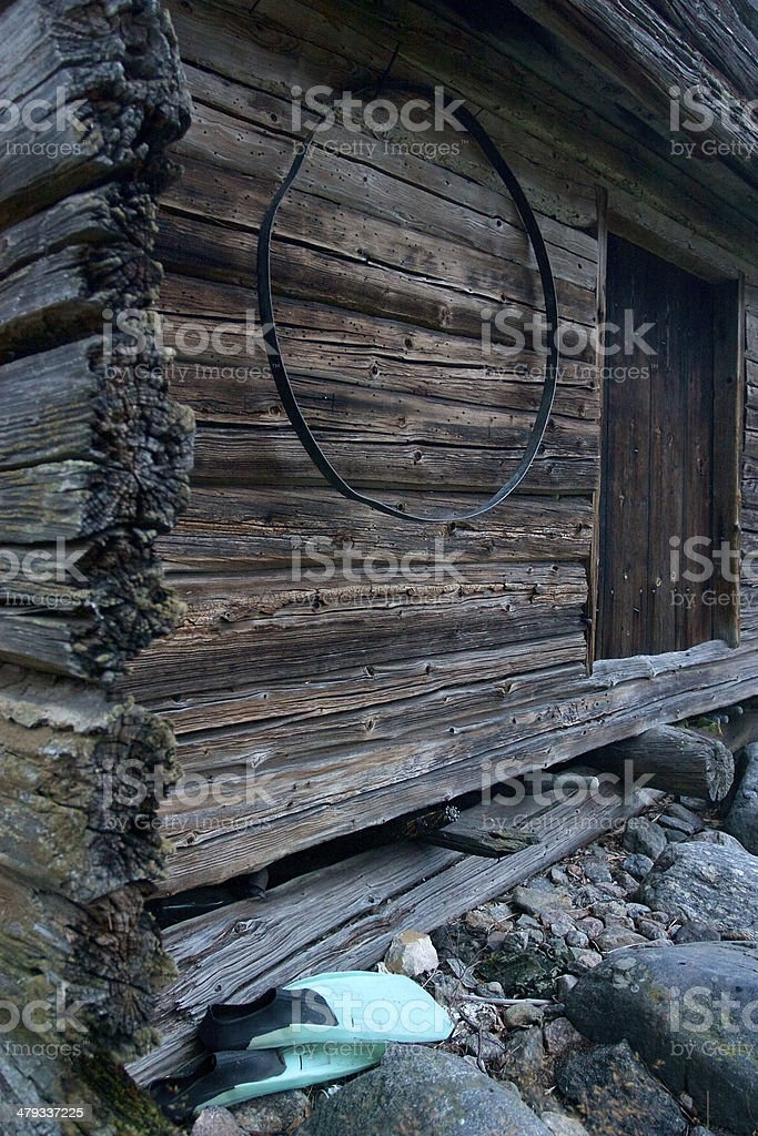 Green fins laying next to wooden shed stock photo