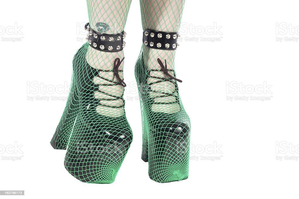 Green fishnets over black platform shoes. stock photo