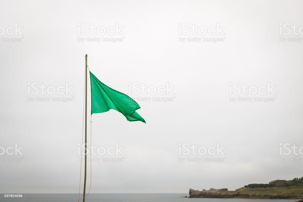 Green flag in the Castro Urdiales beach, Spain stock photo