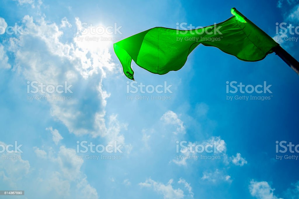 Green flag on a background of the dark blue sky stock photo