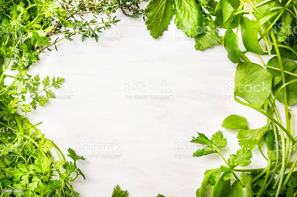 Green fresh herbs mix on white wooden background , top view stock photo