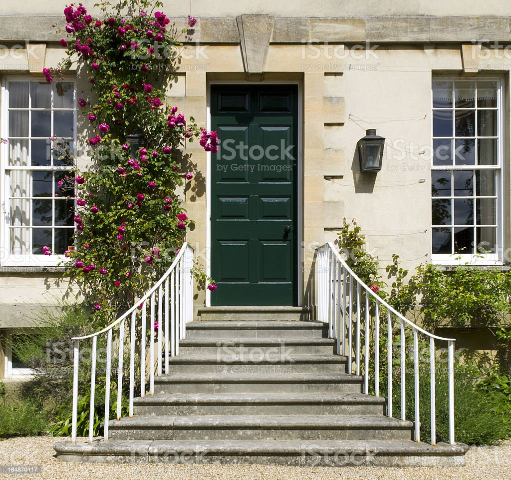 A green front door with flowers growing royalty-free stock photo