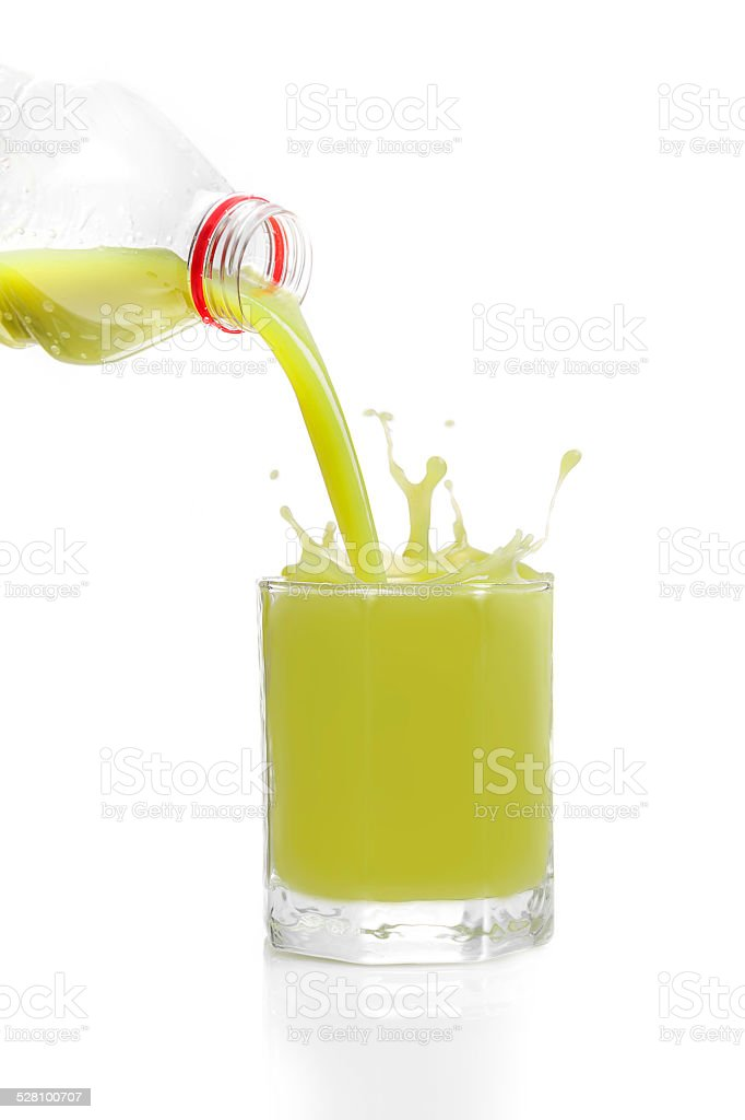 Green fruit juice from kiwis, lime, grapes pored from bottle stock photo