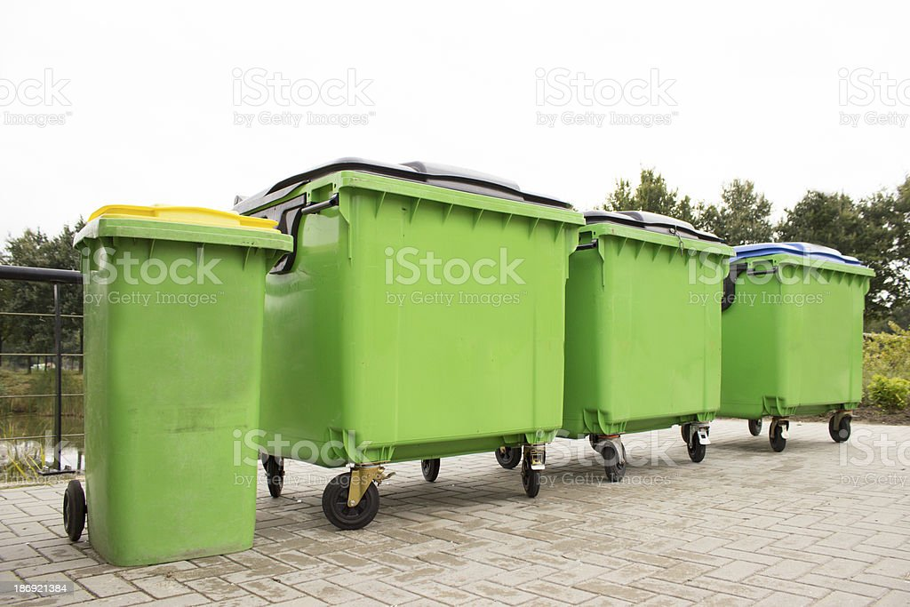 Green garbage containers in a row stock photo