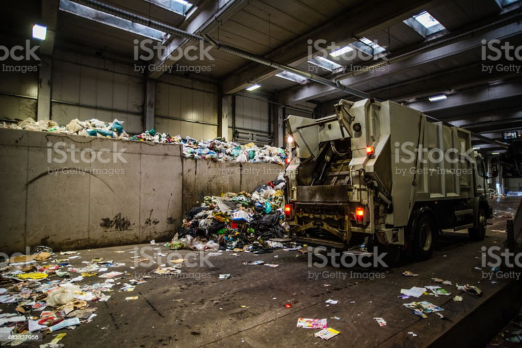Green garbage truck at recycling plant stock photo