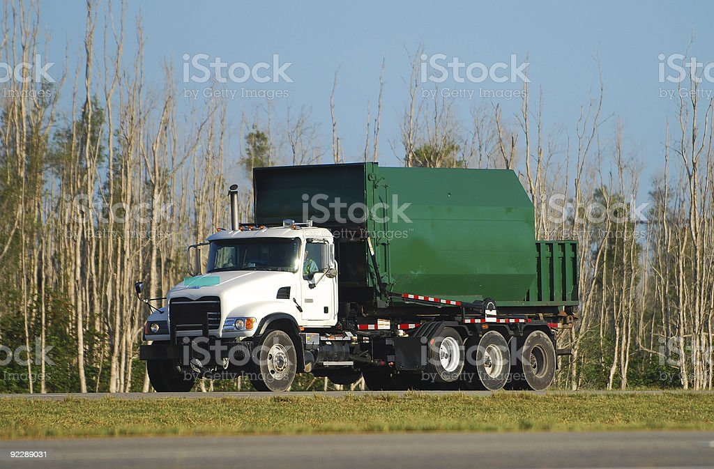 Green garbage truck driving down the road stock photo
