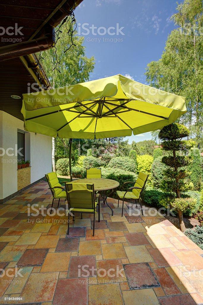 Green garden furniture with sunshade stock photo