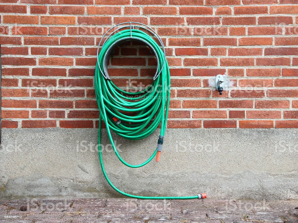 Green Garden Water Hose mounted on Red Brickwall stock photo
