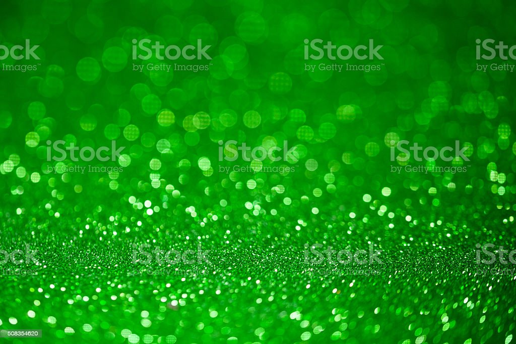 Green glitter surface with green light bokeh stock photo