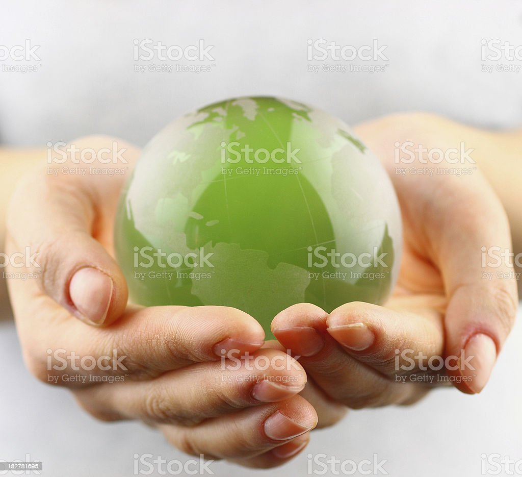 Green globe in  hands stock photo