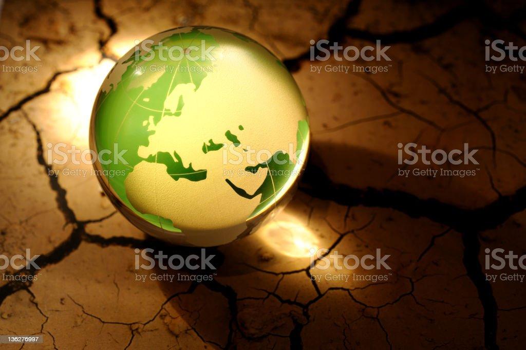 Green globe on cracked dirt stock photo